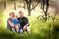 Sitting in grassy field, Erin and Jeremiah Bishop hold their son. A bicycle leans against tree in background